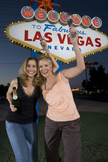 Portrait of excited female friends with champagne against 'Welcome to Las Vegas' sign