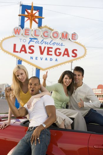 Portrait of excited friends with car and 'Welcome To Las Vegas' sign in the background