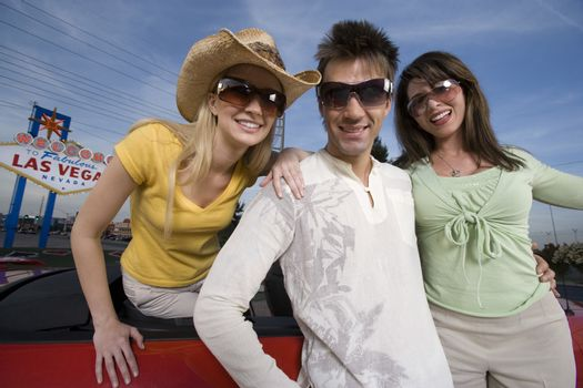 Portrait of a happy friends wearing sunglasses with car and signboard in the background