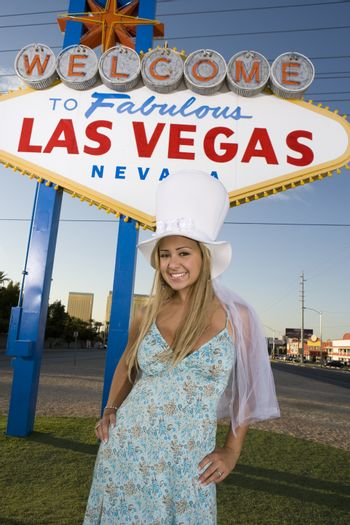 Portrait of an attractive woman standing with 'Welcome To Las Vegas' sign in the background