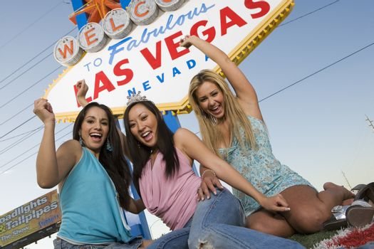 Three women in front of Las Vegas welcome sign Nevada USA