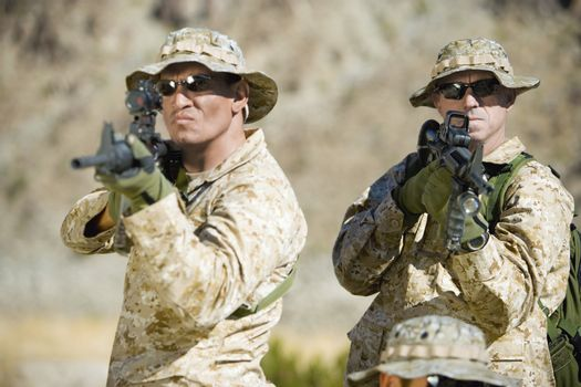 Confident soldiers in uniform aiming rifles