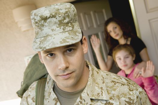 Confident military man leaving house with family waving in background