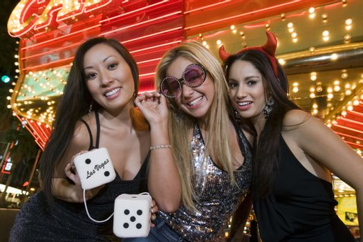 Portrait of three young women with fuzzy dice in front of illuminated casino Las Vegas Nevada USA