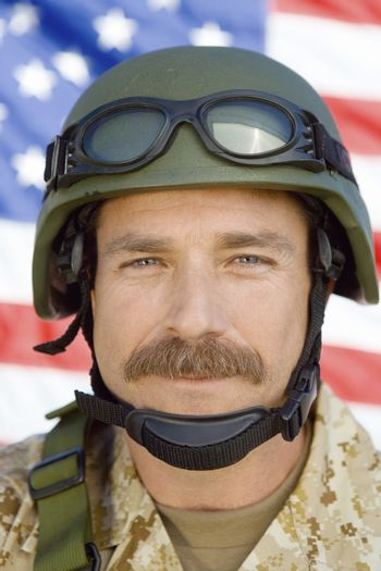 Closeup portrait of a soldier with moustache in front of United States flag