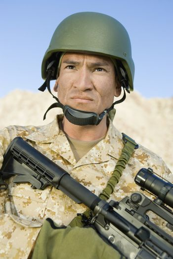 Confident soldier in uniform with sniper rifle