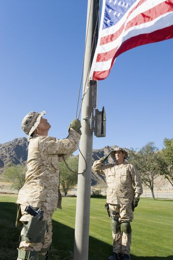 Soldiers raising United States flag against the sky