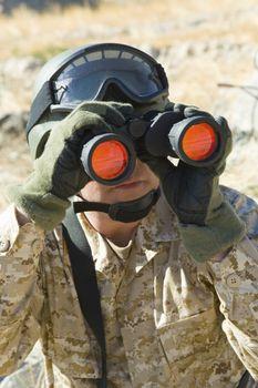 Middle aged soldier looking through binoculars while patrolling during war