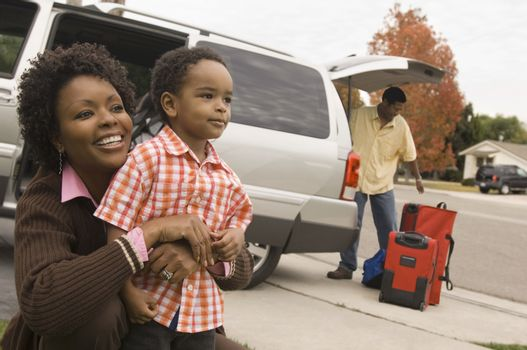 Mother with son and man loading baggage in boot of car