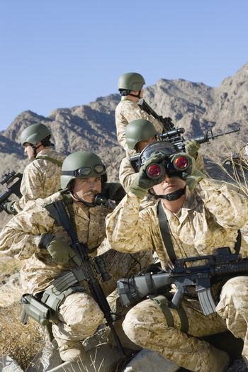 Group of soldiers with rifles and binocular patrolling during war