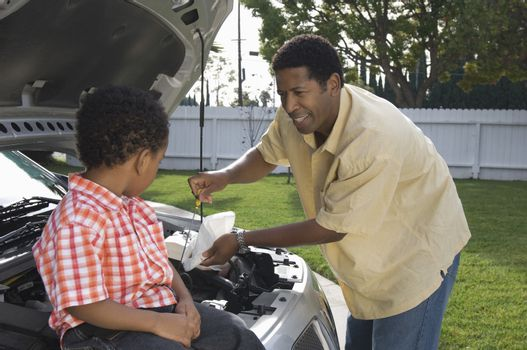 Little boy looking at father checking engine oil of a car