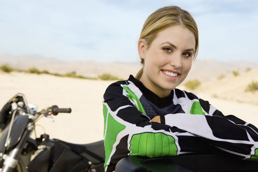 Portrait of happy female off road motor biker with hands folded