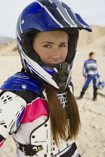 Portrait of female motor biker with man in the background at track