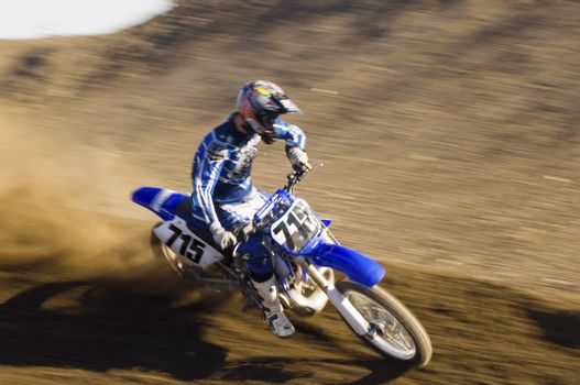 Young motocross racer riding motorcycle on dirt track