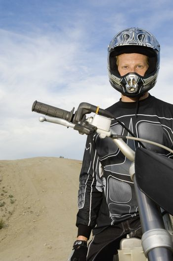 Portrait of male off road motor bike rider with motor bike at racing track against sky