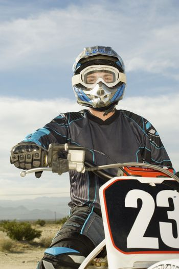Portrait of male off road motor bike rider with motor bike at track against sky