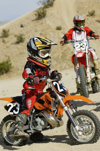 Teenage motocross rider with mother in the background