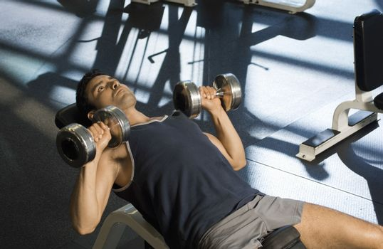 Determined man exercising with dumbbells in health club