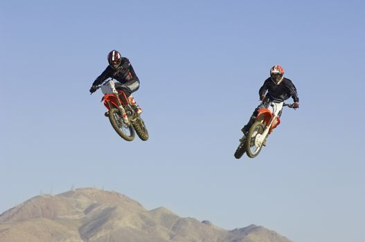 Two male motocross racers performing stunt in midair against clear blue sky