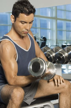 Healthy man lifting weights at a gym