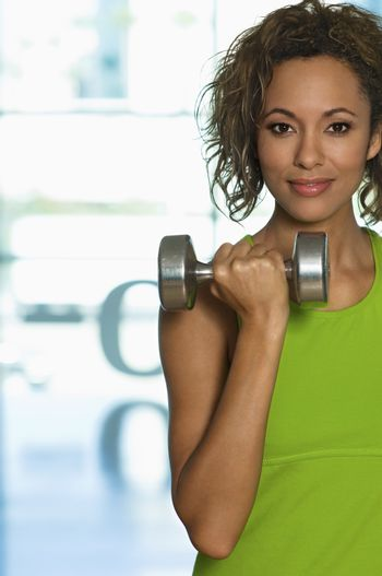 Portrait of confident young woman lifting dumbbell in health club