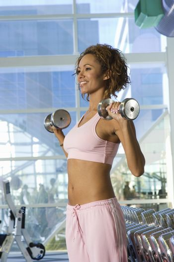 Happy mixed race woman lifting weights in health club