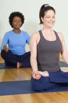 Happy women meditating in lotus position