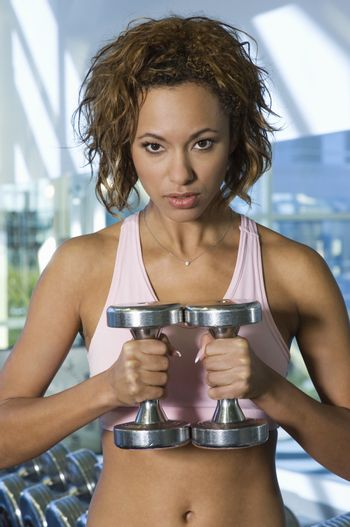Portrait of confident beautiful woman lifting dumbbells in health club