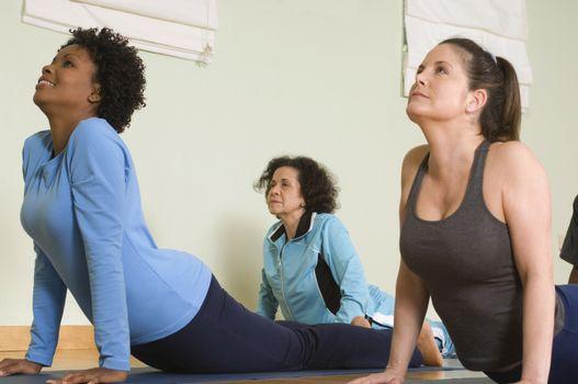 Multi ethnic women performing yoga