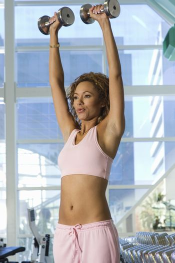 Mixed race woman lifting weights in health club
