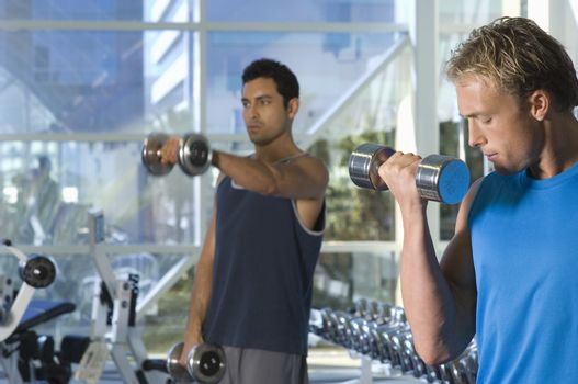 Handsome men lifting weights at a gym