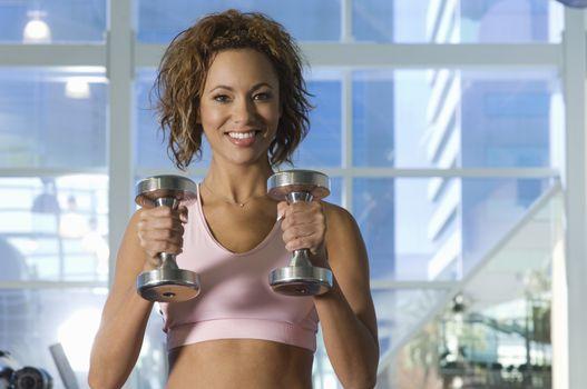 Portrait of happy beautiful woman lifting dumbbells in health club