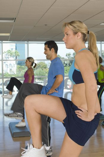 Man and women doing stepping exercise in gym