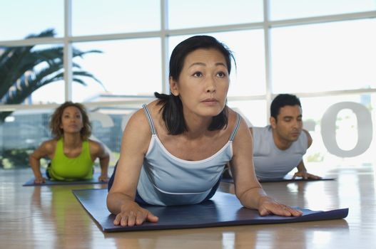 Multi ethnic people exercising on mat