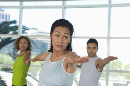 Multi ethnic people performing stretching exercise