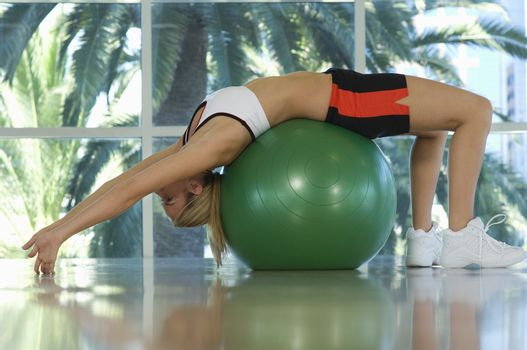 Woman Bending Backwards Over Exercise Ball