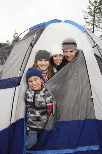 Happy family of four peeking heads out of tent