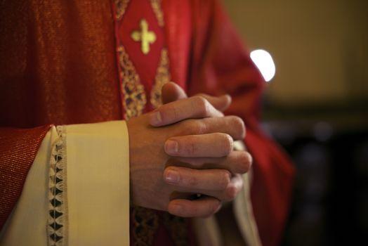 Catholic priest on altar praying during mass
