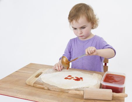 little girl making pizza. studio shot on light grey background