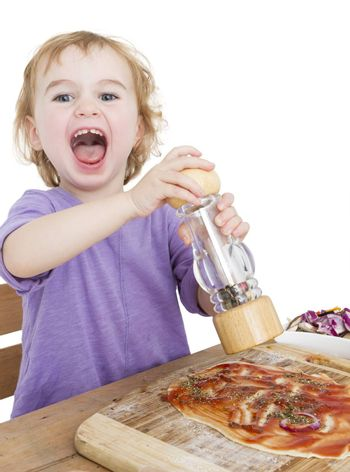 child with pepper making fresh pizza. studio shot isolated on white background