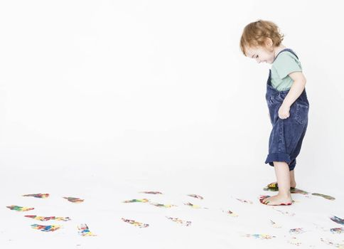 girl making colored footprints on the floor. studio shot with light grey background