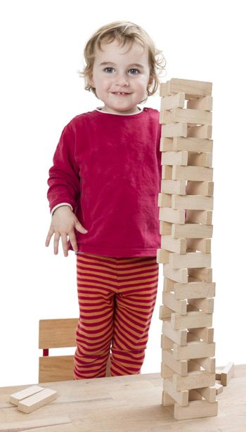 child with tower made of toy blocks. studio shot isolated on white background
