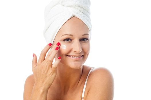 Charming woman applying lotion on her face