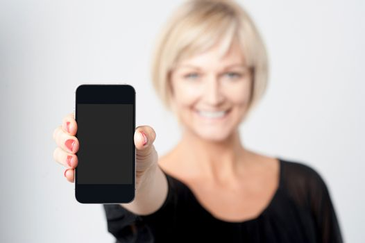 Woman displaying new phone in market
