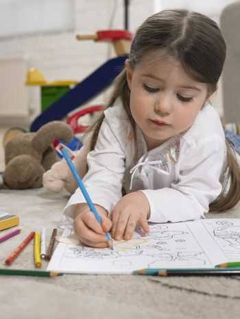 Cute little girl coloring book on floor at home