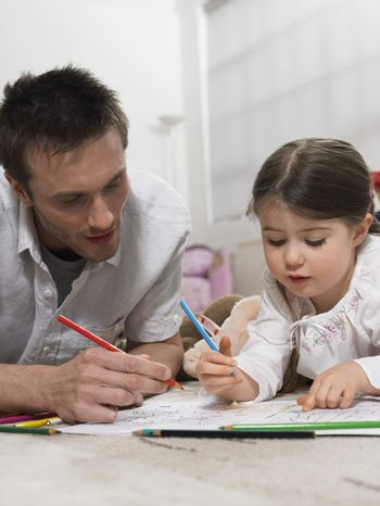 Father and daughter coloring book together on floor at home
