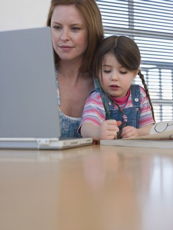 Mother using laptop while daughter coloring at table in house