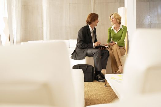 Happy businesspeople communicating over organizer in office lobby