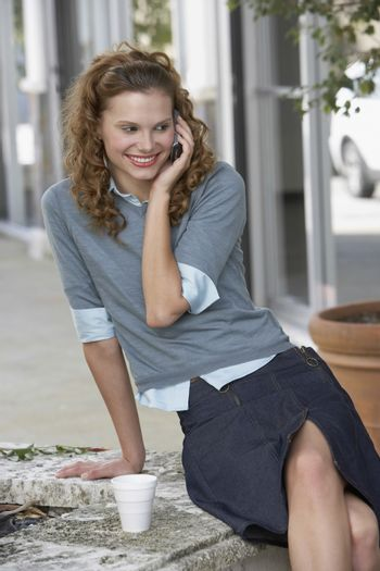Happy young businesswoman with disposable cup using mobilephone