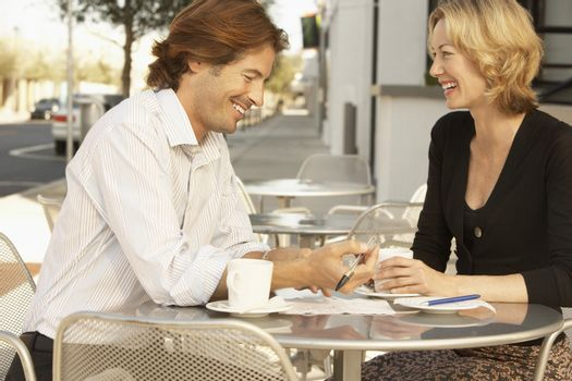 Happy businesspeople with documents sitting at outdoor cafe